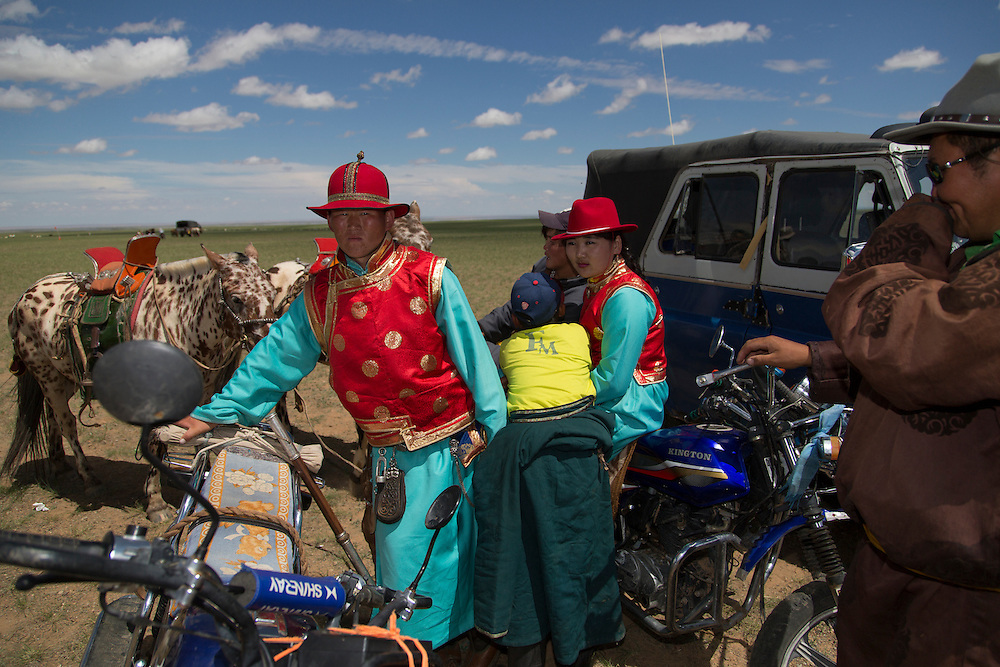A couple dressed in matching deel waits to compete in a best-dressed competition of the Naadam Festival at the Three Camel Lodge in the Gobi Desert of Mongolia on July 31, 2012..
