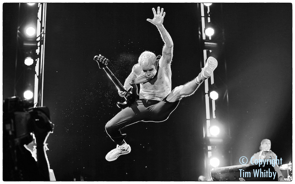 (EDITORS NOTE: IMAGE HAS BEEN PROCESSED USING DIGITAL FILTERS)  NEWPORT, ISLE OF WIGHT - JUNE 14:  Flea of Red Hot Chili Peppers performs at The Isle of Wight Festival as Seaclose Park on June 14, 2014 in Newport, Isle of Wight.