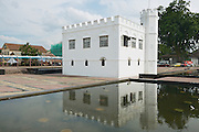 KUCHING, MALAYSIA - AUGUST 26, 2009: Exterior of the white historical building reflected in the water of the pond in Kuching, Malaysia.