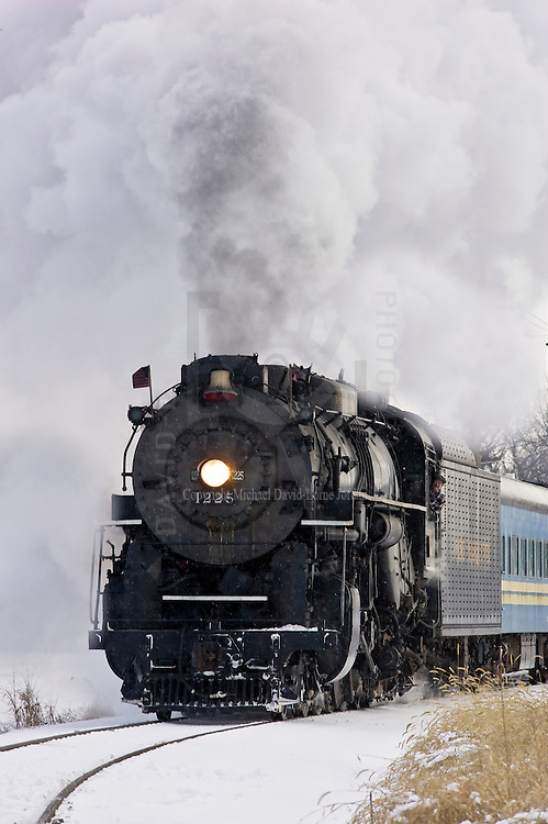 """1225 Pere Marquette steam locomotive under power pulling a """"North Pole Express """" passenger train."""