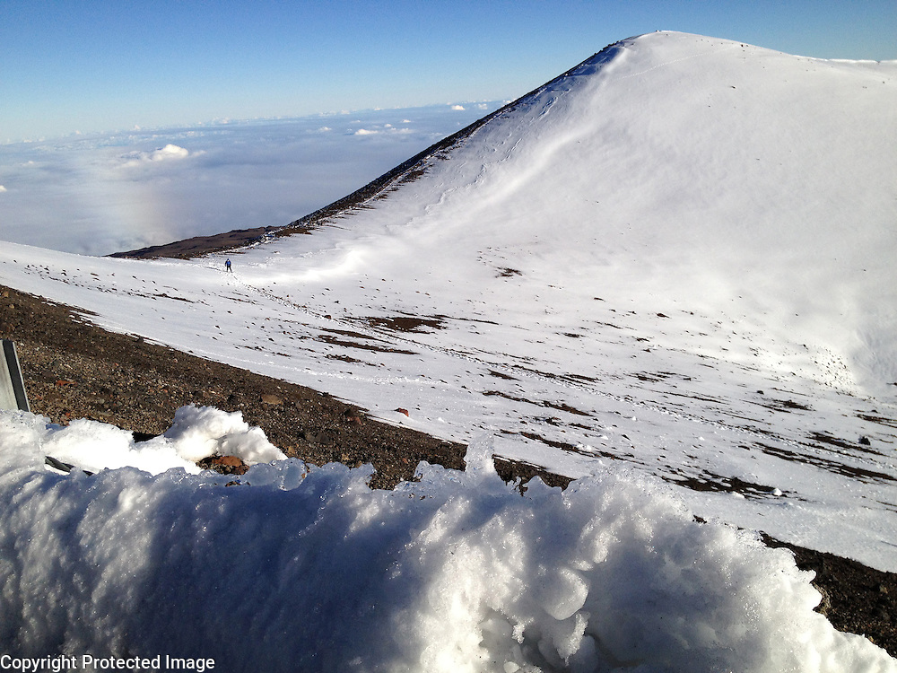 A man walks to the snow covered peak of Mauna Kea on the Big Island of Hawaii. Mauna Kea is 13,796ft high but from from the bottom of the ocean, is the tallest mountain in the world at 33,500ft.  Due to its high altitude, dry environment and isolated geographical location, Mauna Kea's summit is one of the best sites in the world for astronomical observation. Since the creation of an access road in 1964, thirteen telescopes funded by eleven countries have been constructed at the summit.