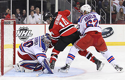 Mar 6; Newark, NJ, USA; New Jersey Devils center Adam Henrique (14) fights New York Rangers left wing Carl Hagelin (62) for the rebound after a save by New York Rangers goalie Henrik Lundqvist (30) during the second period at the Prudential Center.