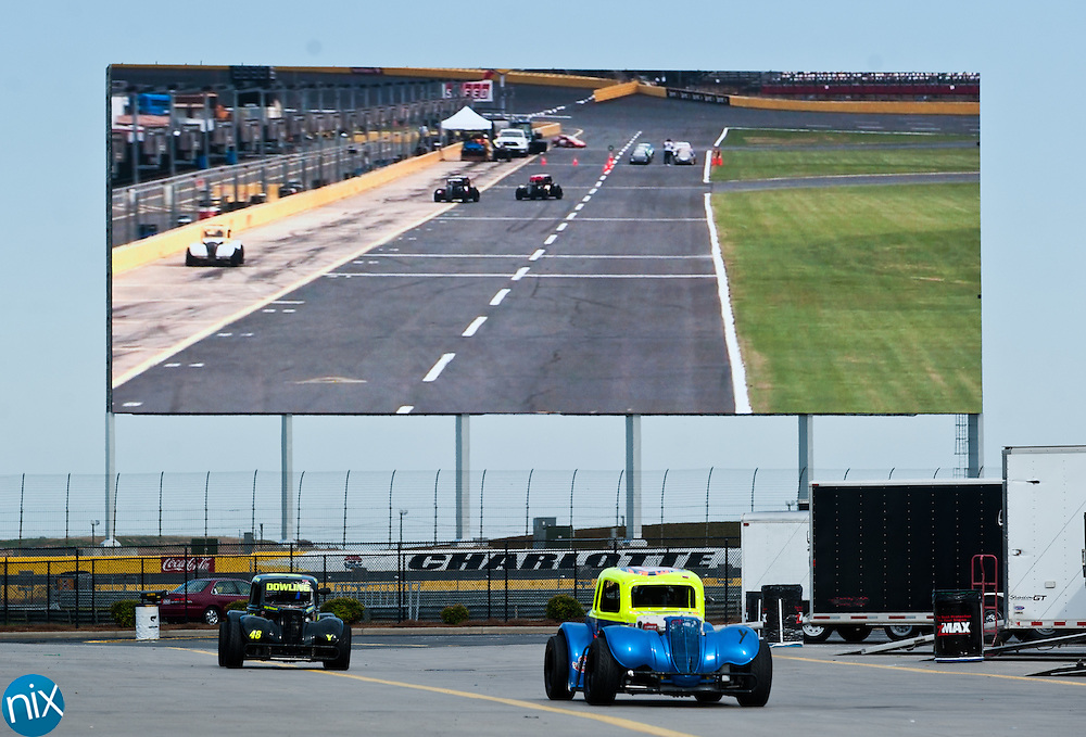 Legends cars pull out of the garage in front the 80-foot tall HD TV at Charlotte Motor Speedway during the second night of the Summer Shootout Tuesday night. The summer racing series will go on through July.  (Photo by James Nix)