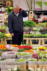© Licensed to London News Pictures. 15/03/2012. London, UK. Terry Smith who has worked at the market for 33 years takes a telephone order. The Mothering Sunday sales rush is on for flower growers, suppliers, florists and retailers amongst the Flowers at the New Covent Garden Flower Market on March 15th 2012 in London, England. New Covent Garden Flower Market is London's premier wholesale market stocking the widest range of flowers, plants and foliage in the UK. The run up to Mothers' Day is crucial in the flower selling calendar as Mothers' Day sales are condensed into about four days making the market very busy. Traditionally, Mothering Sunday was a day when children, mainly daughters, who had gone to work as domestic servants, were given a day off to visit their mother and family. Today, Mother's Day is a time when children give flowers and cards to their mothers, and generally pamper them..  Photo credit : Stephen SImpson/LNP