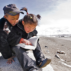 Children reading a book nar the Pamir highway, Tajikistan, Asia