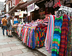 Scarfs, yardage, and dresses lure customers to this shop on West Street, Yangshou. Yangshuo is a county and city under the jurisdiction of Guilin City, in the northeast of Guangxi Province, China. Its seat is located in Yangshuo Town. Surrounded by karst peaks and bordered on one side by the Li River it is easily accessible by bus or by boat from nearby Guilin. It is a major tourist and resort destination for Chinese and foreigners alike.