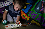 Lucas (5) reads books at the children's makeshift den at home in Shefield UK Tuesday, Aug. 12, 2014The D'Arby family is involved in the FAST  (Families and Schools Together) program which encourages parents to read to their children at home.(Elizabeth Dalziel for Save the Children )