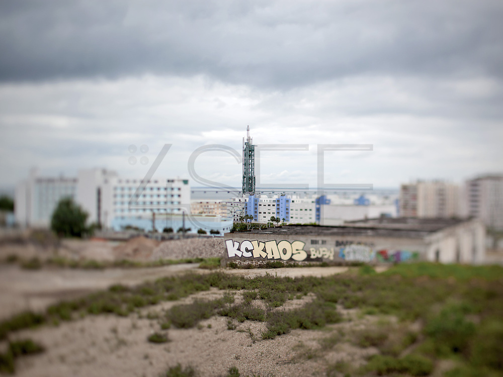 Land waiting for future constrution, north of the river Tejo (Tagus). In the centre of the image, the Galp Tower is a simbol of the old industrial area of Lisbon where was born the Expo'98, The World Exhibition of Lisbon. This photograph is part of a body of work about Lisbon, feelings, affections and loneliness. Is about a city depressed by the crisis, but even so, tolerant and cosmopolitan.