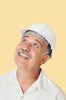 Senior man with hardhat looking up and smiling over yellow background