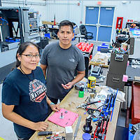 Wynona Wilson, left, and Shane Tsosie pose with parts of an air powered engine they built at Navajo Technical University manufacturing lab in Crownpoint Thursday. The two spent three months researching manufacturing at the University of North Carolina - Charlotte and have brought back knowledge and experience for NTU.