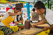 17 OCTOBER 2012 - BANGKOK, THAILAND:   Men use mallets to pound out Thai peanut brittle during the Vegetarian Festival food fair on Yaowarat Road in Bangkok's Chinatown. The Vegetarian Festival is celebrated throughout Thailand. It is the Thai version of the The Nine Emperor Gods Festival, a nine-day Taoist celebration celebrated in the 9th lunar month of the Chinese calendar. For nine days, those who are participating in the festival dress all in white and abstain from eating meat, poultry, seafood, and dairy products. Vendors and proprietors of restaurants indicate that vegetarian food is for sale at their establishments by putting a yellow flag out with Thai characters for meatless written on it in red.     PHOTO BY JACK KURTZ