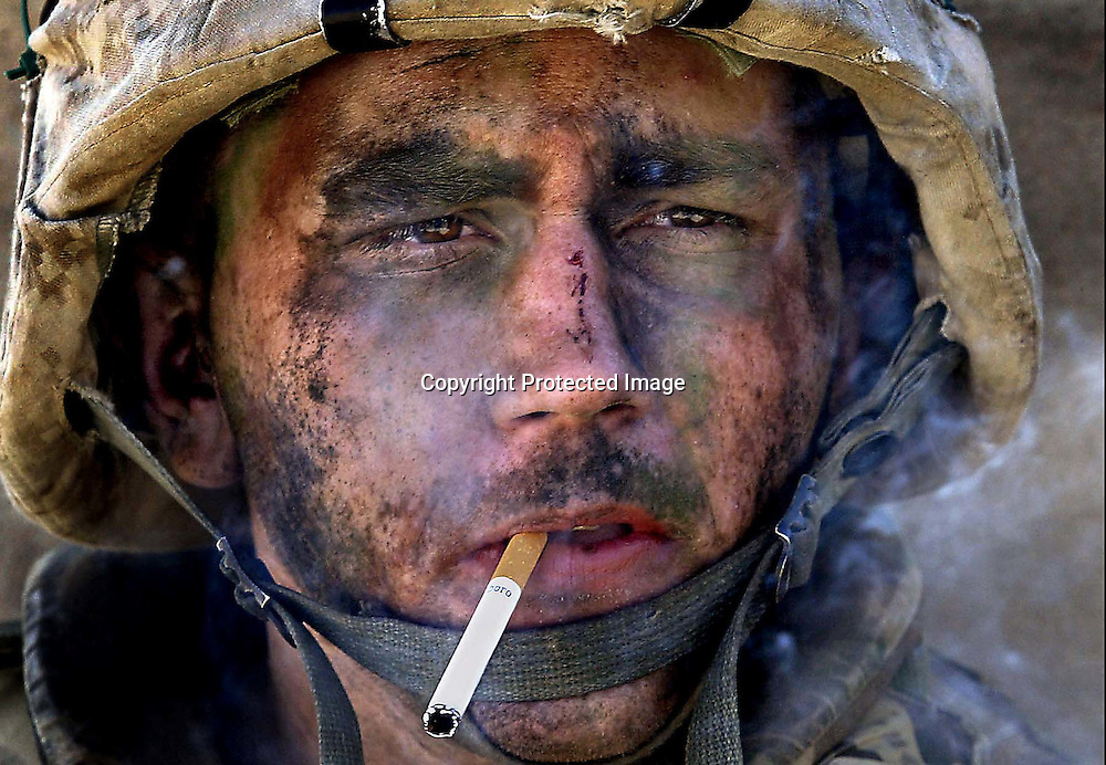 "Marine Lance Cpl. James Blake Miller, 20, of Kentucky, a member of Charlie Company of the U.S. Marines First Division, Eighth regiment, smokes a cigarette in Fallujah, Iraq, Nov. 9, 2004. Miller came to be known as the ""Marlboro Man"" for this iconic photograph from the Iraq War. (Luis Sinco/Los Angeles Times)"