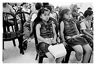 Two twin girls waiting in the audience at the local Red Cresent building to see a concert. Qalqilia, Palestine, 2007