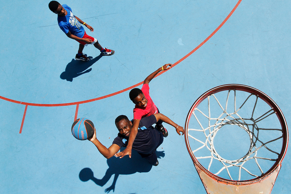 Joseph Ugonna, of Atlanta, center, drives the ball to the hoop, while his son Chima Ugonna, 13, hangs over his shoulder in an attempt to block his shot, meanwhile Ikechi Ugonna, 14, left, watches from the top of the lane while shooting hoops at The Bristol Sports Arena on Hilton Head Island on April 6, 2015. Joseph Ugonna is a Big 10 guy and picking Wisconsin over Duke in tonights NCAA Championship game, however both sons are picking Duke to win it all.