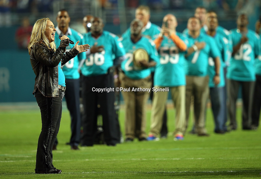 Melissa Etheridge sings the National Anthem before the Miami Dolphins NFL week 14 regular season football game against the New York Giants on Monday, Dec. 14, 2015 in Miami Gardens, Fla. The Giants won the game 31-24. (©Paul Anthony Spinelli)