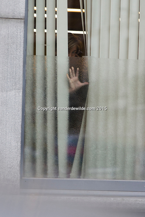 2015 november 16. Brussels, Belgium, Sint Jans Molenbeek.A neighbor of the house of the Abdeslam family looking out of her window at the press.