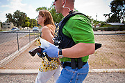 21 SEPTEMBER 2010 - PHOENIX, AZ: Detective Cory Geffre (CQ GREEN SHIRT RIGHT) carries a .357 magnum revolver confiscated in a drug arrest while he escorts Donna Conner (CQ BY PHOENIX PD) to a waiting vehicle after she was arrested on drug charges in central Phoenix Tuesday. Crime has steadily dropped in Phoenix over the past few years, in line with national trends. The latest number released this month showed Phoenix reported fewer 2010 homicides, rapes, robberies, thefts - in addition to other major crimes -- compared with the same time period the previous year. Detectives in the Phoenix police department's Major Offender Unit make several arrests every day.   PHOTO BY JACK KURTZ