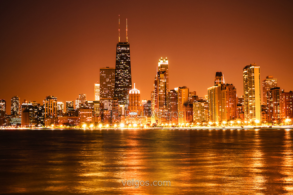 Photo of Chicago at night with Chicago skyline downtown city buildings and the famous John Hancock Center building. The John Hancock Center is one of the world's tallest skyscrapers and is a popular fixture in the Chicago skyline. Photo is high resolution, toned orange and was taken in 2012.