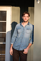 handsome man with dark hair and scruffy face on a porch