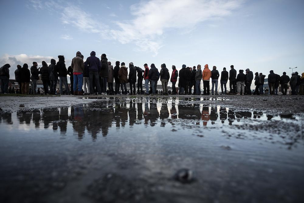 La coda per il pasto giornaliero offerto dalle associazioni umanitarie. <br /> Calais (FR), all'imbarco dei traghetti per il regno unito, dopo il rafforzamento dei controlli, il numero di migranti cresce ogni giorno, nonostante i centri d'accoglienza siano stati amliati i migranti trovano riparo come possono all'interno di una foresta vicino alla strada che porta all'imbarco. In questo modo possono provare a nascondersi sui Camion, ma il numero sempre maggiore di persone sta creando una citt&agrave; parallela di gente senza identit&agrave;.
