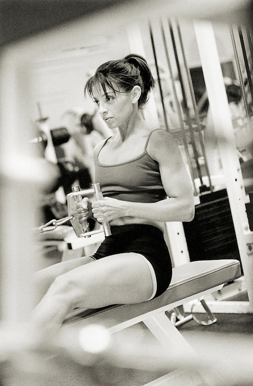 Woman exercising in gym doing seatede rows (B&W)