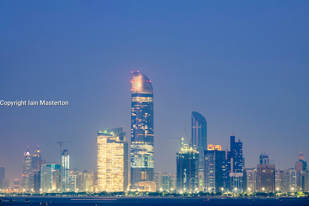 Skyline of modern skyscrapers at night along Corniche in Abu Dhabi United Arab Emirates