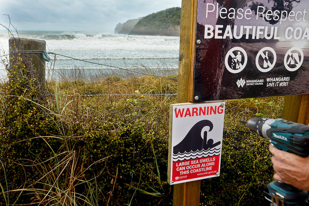 Better late than never, a warning sign is erected as waves caused by Cyclone Pam lash Matapouri, near Whangarei, New Zealand, Monday March 16, 2015. Credit:SNPA / Malcolm Pullman