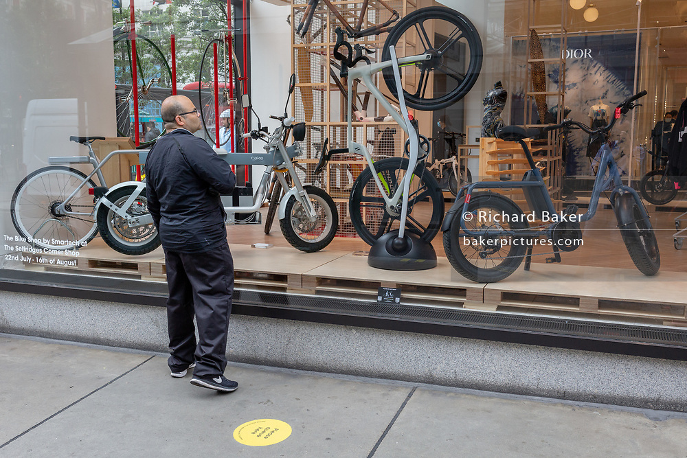 On the day that covid pandemic guidelines for shoppers in England mean that the wearing of face coverings in shops is mandatory, a window shopper looks at bikes and cycling products in Selfridges on Oxford Street, on 24th July 2020, in London, England.
