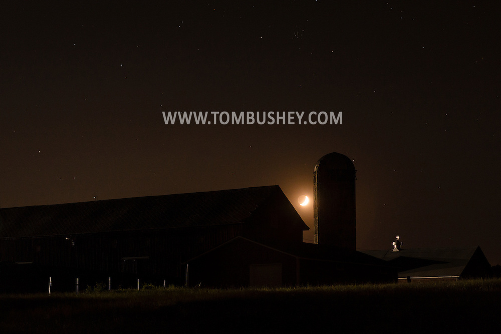 Campbell Hall, New York - The waning crescent moon sets over a barn on a farm on  May 22, 2015.