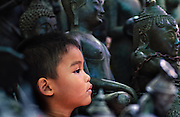 A boy amongst Buddha statues at a market in Bangkok, Thailand.
