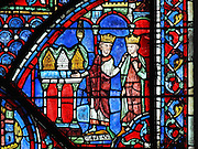 Constantine, Emperor of the East, offers 3 gold and silver reliquaries to Charlemagne as a gesture of thanks for delivering the Holy Land. They may contain the crown of thorns, a piece of the true cross and the shroud of Christ. This section may attest to the authenticity of Chartres' relics. Section of Constantine offering relics to Charlemagne, from the Charlemagne window, early 13th century, in the ambulatory of Chartres Cathedral, Eure-et-Loir, France. Chartres cathedral was built 1194-1250 and is a fine example of Gothic architecture. Most of its windows date from 1205-40 although a few earlier 12th century examples are also intact. It was declared a UNESCO World Heritage Site in 1979. Picture by Manuel Cohen
