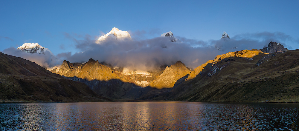 Cordillera Huayhuash reflects in Carhuacocha lake (13,600 feet) in the Andes Mountains, Peru, South America. Peaks from left to right are: Siula Grande, Yerupaja Grande (6635 m or 21,770 ft, highest point in the Amazon watershed), Yerupaja Chico, and Mount Jirishanca (Icy Beak of the Hummingbird). Day 3 of 9 days trekking around the Cordillera Huayhuash. This panorama was stitched from 3 overlapping photos.