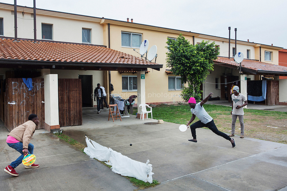 MINEO, ITALY - 26 NOVEMBER 2014: Asylum seekers from Nigeria and Gambia play entry way of a house of the CARA (Accommodation Centre for Asylum Seekers) in Mineo where approximately 4,000 asylum seekers live, in Mineo, Italy, on November 26th 2014.<br /> <br /> By law, asylum-seekers can be held for 35 days in a CARA. In reality, the average stay is closer to a year.The Cara is located at the &quot;Residence degli Aranci&quot; (Residence of the Oranges), a small town built to accomodate the families of US soldiers operating at the Naval Air Station of Sigonella 40km away. Since 2011 the &quot;Residence degli Aranci&quot; hosts the Accommodation Center for Asylum Seekers, which has since then hosted more than 12,000 seekers of 47 nationalities and over 200 ethnic groups. The CARA of Mineo includes 404 houses. Each house hosts from 7 to 11 asylum seekers.