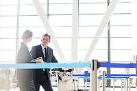 Mature businessman talking with his business partner in check in are at airport