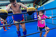 """18 DECEMBER 2104 - BANGKOK, THAILAND: A girl who wants to box works out next to a boxer after a sparring session at the Kanisorn gym. The Kanisorn boxing gym is a small gym along the Wong Wian Yai - Samut Sakhon train tracks. Young people from the nearby communities come to the gym to learn Thai boxing. Muay Thai (Muai Thai) is a Thai fighting sport that uses stand-up striking along with various clinching techniques. It is sometimes known as """"the art of eight limbs"""" because it is characterized by the combined use of fists, elbows, knees, shins, being associated with a good physical preparation that makes a full-contact fighter very efficient. Muay Thai became widespread internationally in the twentieth century, when practitioners defeated notable practitioners of other martial arts. A professional league is governed by the World Muay Thai Council. Muay Thai is frequently seen as a way out of poverty for young Thais and Muay Thai camps and schools are frequently crowded. Muay Thai professionals and champions are often celebrities in Thailand.     PHOTO BY JACK KURTZ"""