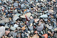 Amber sea glass among the stones on the beach at Welshpool, New Brunswick.