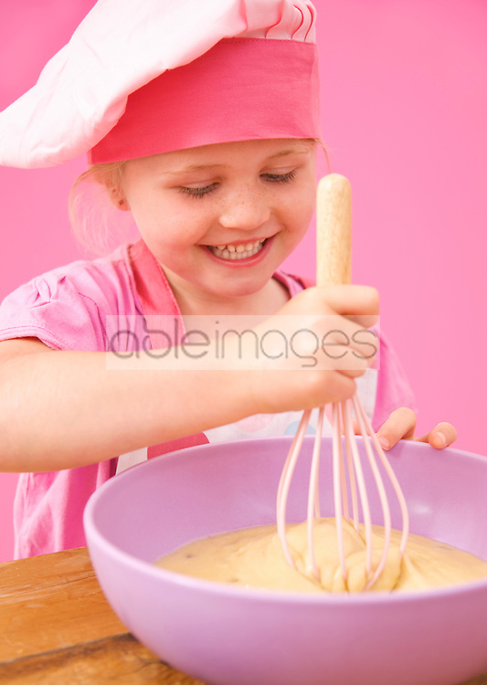 Close up of a smiling young girl whisking cake mix