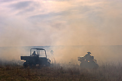 "Workers of the Flying W Ranch near Clements, Kansas control the burning of ranch prairie during the ""Flames in the Flint Hills."" This agritourism event allows guest to the ranch take part in lighting the prescribed burns. Prairie grasses in the Kansas Flint Hills are intentionally burned by land mangers and cattle ranchers in the spring to prepare the land for cattle grazing and help maintain a healthy tallgrass prairie ecosystem. The burning is also an effective way of controlling invasive plants and trees. The prairie grassland is burned when the soil is moist but grasses are dry. This allows the deep roots of the grasses to survive and the burned grasses on the soil surface return as nutrients to the soil. These nutrients allow for the rapid growth of new grass. After approximately two weeks of burning, new grass emerges. Less than four percent of the original 140 million acres of tallgrass prairie remains in North America. Most of the remaining tallgrass prairie is in the Flint Hills in Kansas."