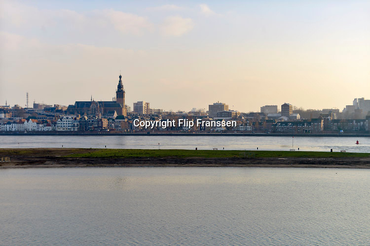 Nederland, Nijmegen, 17-2-2016 De bijna 4 km. lange nevengeul aan de overkant van de Waal bij Lent is volgelopen vanwege hoogwater in de Waal. Grootste onderdeel van de vele werken van Rijkswaterstaat om bij hoogwater een betere waterafvoer in de rivier te hebben. Het dorp veurlent ligt op een kunstmatig eiland.  Ruimte voor de rivier, water, waal. In de nieuwe dijk is een drempel gebouwd die stapsgewijs water doorlaat en bij hoogwater overloopt. The Netherlands, Nijmegen Measures taken by Nijmegen to give the river Waal, Rhine, more space to flow during highwater and to prevent the risk of flooding. Room for the river. Reducing the level, waterlevel. Large project to create a new paralel gully, an extra flow of water, so the river can drain more water during highwater. Due to climate change and expected rise, increase of the sealevel, the Dutch continue to protect their land from the water. Foto: Flip Franssen/HH