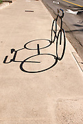 A bicycle shaped sidewalk bicycle rack with shadow in Waikiki.