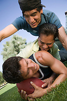 Three young men playing football.