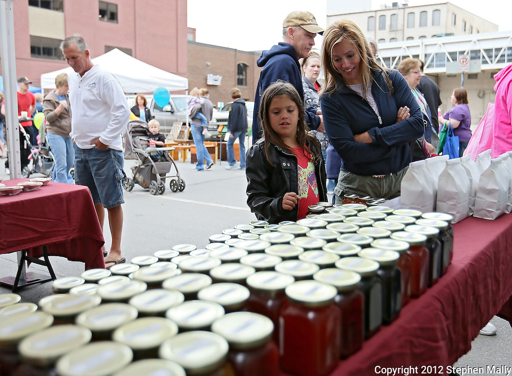 Kiran Burns (from left), 9, and her mother Val Burns, of Walford, look over the various jellies and jams for sale at the Barb's Garden & Pantry booth at the Downtown Farmers' Market in Cedar Rapids on Saturday morning, June 2, 2012. There were 244 vendors who participated in the first market of the year. (Stephen Mally/Freelance)