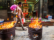 "10 AUGUST 2014 - BANGKOK, THAILAND:     A man walks by barrels burning joss paper and hell money in front of a home in a back alley in the Chinatown section of Bangkok. The seventh month of the Chinese Lunar calendar is called ""Ghost Month"" during which ghosts and spirits, including those of the deceased ancestors, come out from the lower realm. It is common for Chinese people to make merit during the month by burning ""hell money"" and presenting food to the ghosts.  PHOTO BY JACK KURTZ"