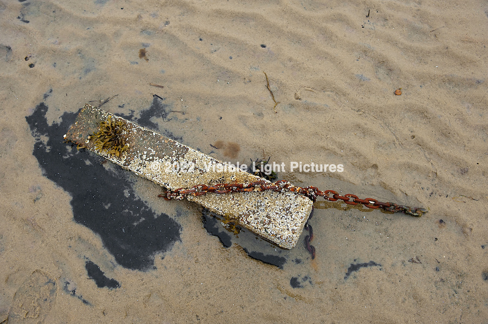 Concrete block with rusted chain on the beach.