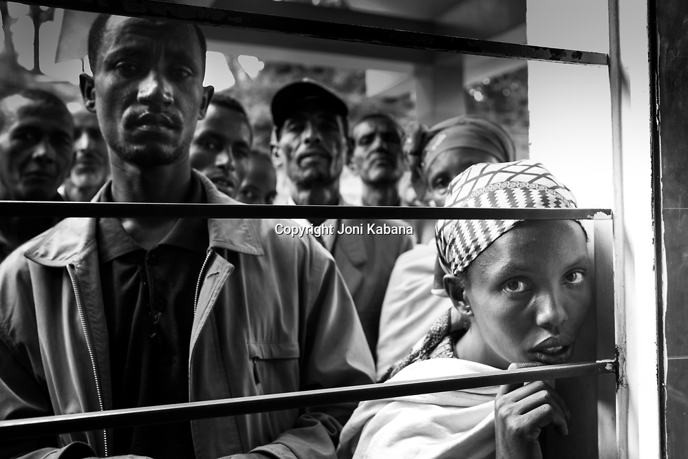 A woman waits with men who support her for a chance to be seen by visiting doctors in rural Ethiopia