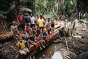 A group of loggers living in a jungle camp downriver from Sawa Village in the Asmat, a large, steamy hot tidal swamp in Irian Jaya, Indonesia. This group is logging the forest with hand axes, dragging the huge hardwood logs from deep in the forest over a long path of smaller cross logs. When they get to the river the logs are lashed together in rafts and floated down the river to sell to traders for cash or outboard boat motors. Image from the book project Man Eating Bugs: The Art and Science of Eating Insects.