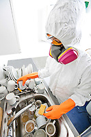 High angle view of woman in gas mask washing utensil at kitchen sink