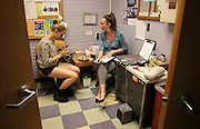Community Health Promotions Specialists Zoe Odlin-Platz, right, waits as a client, left, prepares to exchange used needles for clean ones at Portland Maine's India Street Public Health Center.  The center distributes one-third of the needles in the state. According to Maine Office of Substance Abuse's treatment data system from 2010 through 2014 the number of heroin addicts seeking treatment more than tripled from 1,115 to 3,463.