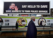 © Licensed to London News Pictures. 03/10/2012. Birmingham, UK A man walks past a banner saying 'Say Hello to Dave, Wave Goodbye To YOur Police Service' opposite the entrance to The Conservative Party Conference at the ICC today 8th October 2012. Photo credit : Stephen Simpson/LNP