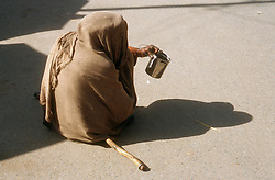 Beggar with walking stick sitting on ground in India holding out a tin can,
